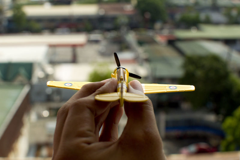 Holding a yellow vintage airplane Airplane Dream Flight Fly Holding Idea Plane Toy Transportation Travel