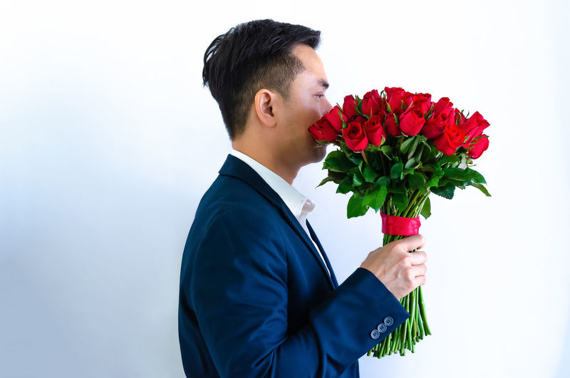 Man holding red rose against white background