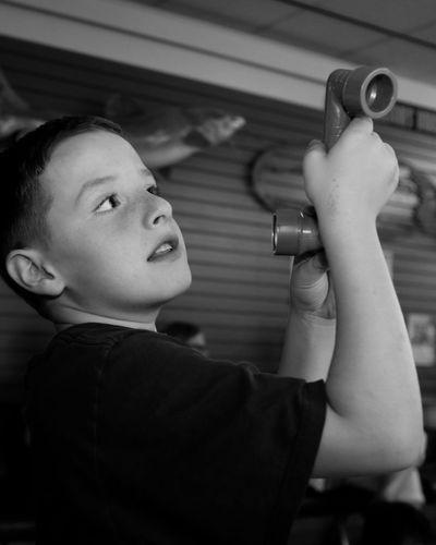 Boy Holding Periscope In Classroom