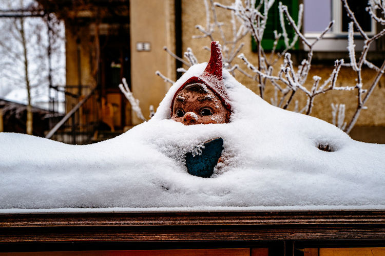 Close-up of garden gnome in snow