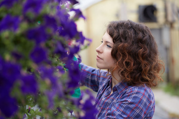 Close-up of woman by purple flowering plants