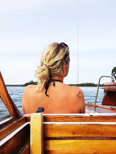 Rear View Of Woman Sitting In Boat Sailing On Sea