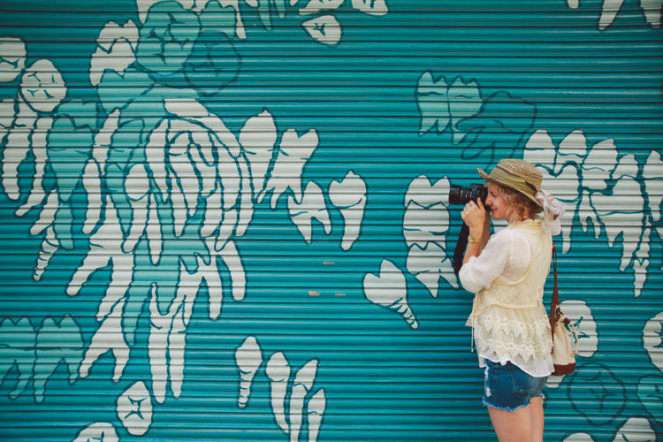 Woman Photographing With Camera Against Shutter