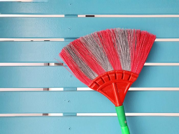 Cobweb broom on blue wall. household equipment concept