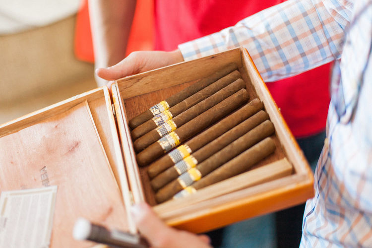 Midsection of man holding cigars in wooden box