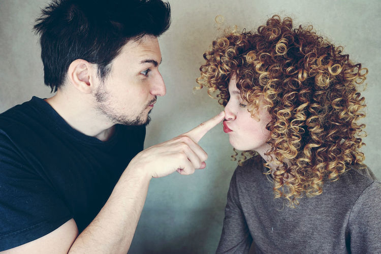 Man Touching Woman Nose Against Wall