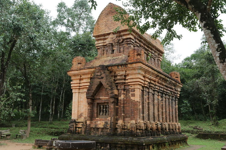 Low angle view of old temple against trees in forest