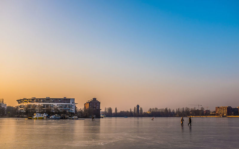 Frozen Lake Architecture Building Exterior Built Structure City Cityscape Clear Sky Day Frozen Nature Nature Outdoors People River Sky Sunset Travel Destinations Urban Skyline Walking On Ice Water Waterfront