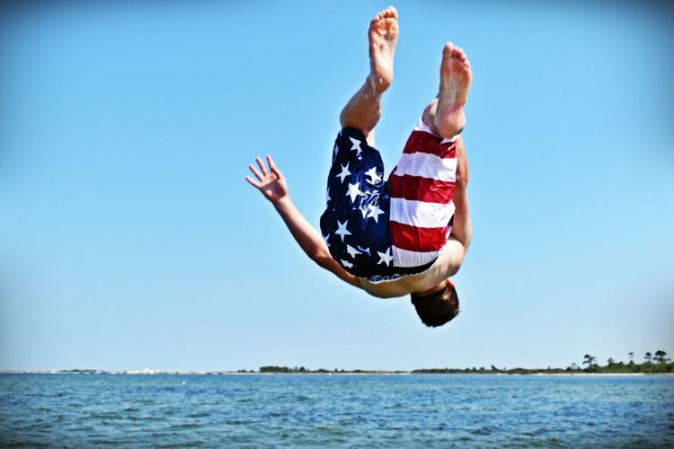 Full Length Of Shirtless Man Backflipping At Beach Against Clear Sky
