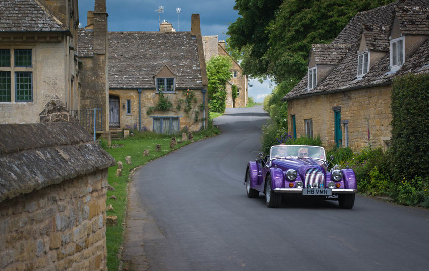 Summer drive in the Cotswolds Classic Car Driving Architecture Building Exterior Built Structure Cotswold Stone Cotswolds Cotswoldvillages Day Drivebyphotography Driving Around Land Vehicle Mode Of Transport No People Open Top Car Outdoors Purple Road Sky Sportscar Transportation Tree