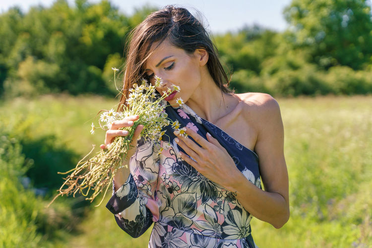Midsection of woman holding plant on field