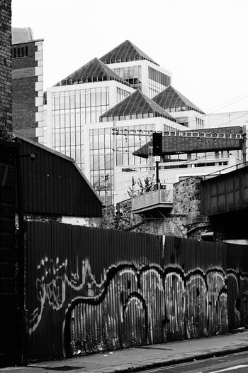 Dublin In Black And White Building Exterior Built Structure Grafitti On Fence Modern Architecture In Dublin New And Old Architecture New Houses Behind Fence No People Out And About In Dublin