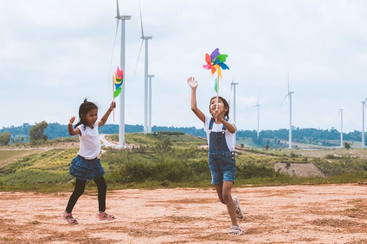 Full length of sisters playing with pinwheel toys on land with windmills in background