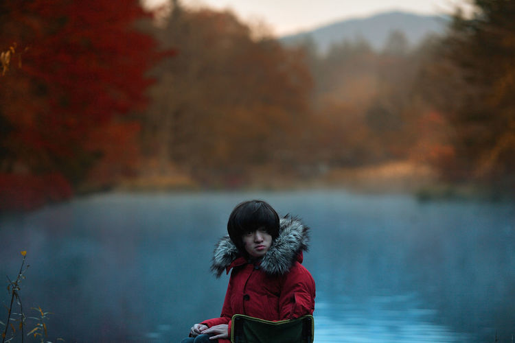 Portrait Of Boy Sitting By Lake