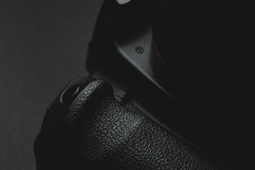 close up view of a DSLR camera Shutter button in dark atmosphere Close-up Indoors  Clothing Portrait Studio Shot Looking At Camera Lifestyles Men Headshot Body Part Front View Leisure Activity Hat Cap Leather Grip Camera Photography DSLR Photographer Gear Shutter Button Video Videography