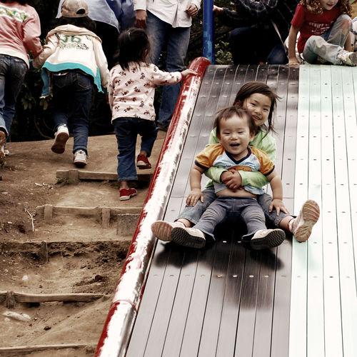 Siblings sliding on slide at park