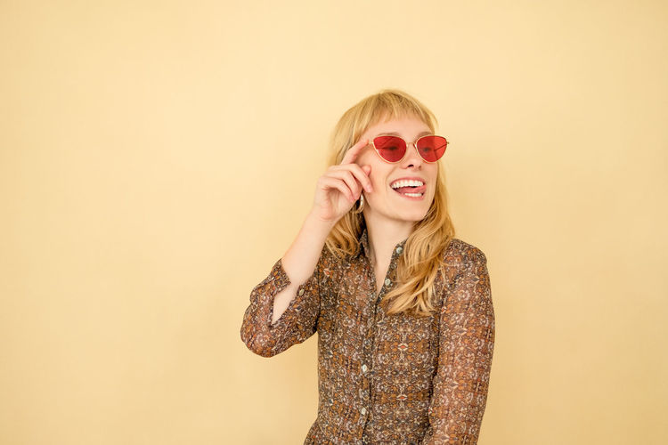 Happy woman in red sunglasses One Person Blond Hair Indoors  Hair Young Women Yellow Color Red Color Well Dressed Beautiful Woman Hairstyle Front View Copy Space Stylish Standing Smiling Young Adult Studio Shot Beige Background Lifestyles Fashion Beauty Moments Of Happiness International Women's Day 2019
