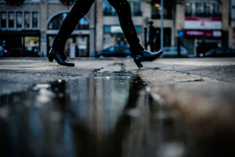 Low Section View Of Woman Walking On Wet Street