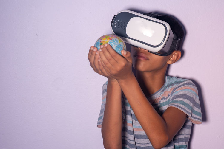 World hold on One Person Wall - Building Feature Indoors  Leisure Activity Casual Clothing Front View Studio Shot Lifestyles Waist Up Child Real People Virtual Reality Simulator Boys Childhood Men Headshot Males  Standing Teenage Boys Teenager Adolescence