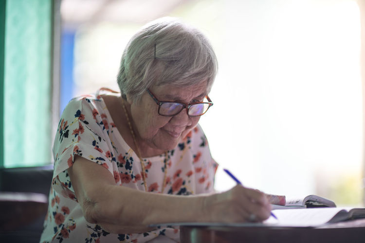 Woman writing in book on table