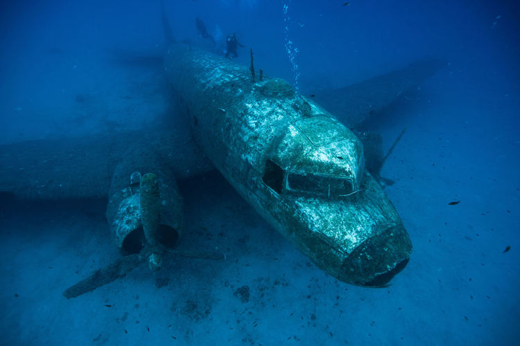 High Angle View Of Scuba Divers Swimming Over Airplane Wreck