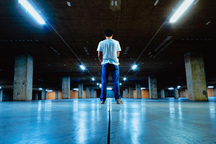 Rear view of man standing at illuminated parking garage