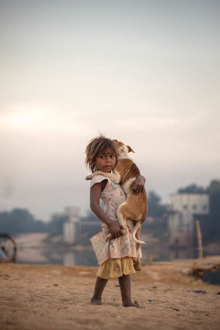 Portrait of girl carrying dog while walking on sand against sky