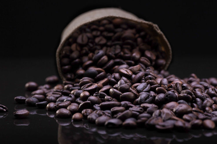 A coffee beans over the black background Food And Drink Coffee Coffee - Drink Roasted Coffee Bean Food Indoors  Freshness Close-up Still Life Brown No People Studio Shot Selective Focus Large Group Of Objects Black Background Caffeine Drink Roasted Abundance Refreshment