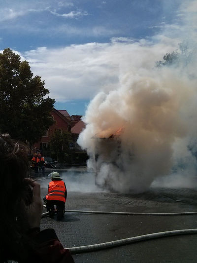 Firefighters extinguishing fire on street against sky