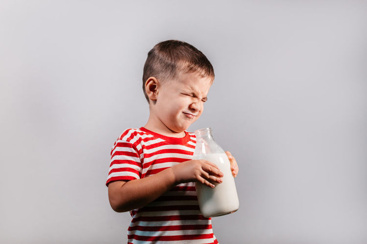 Front view of child with bottle of milk against grey background. Portrait of young boy with eyes closed making faces isolated over gray background - studio shot. Child Striped One Person Drink Drinking Boy Milk Bottle Red Color T-shirt 3-5 Years Grey Gray Background Isolated Studio Shot Indoor Caucasian Horizontal Helth Healthy Eating Dairy Portrait Eyes Closed  Making A Face
