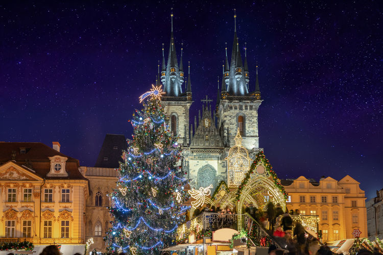 Decorated christmas tree outside tyn church at night