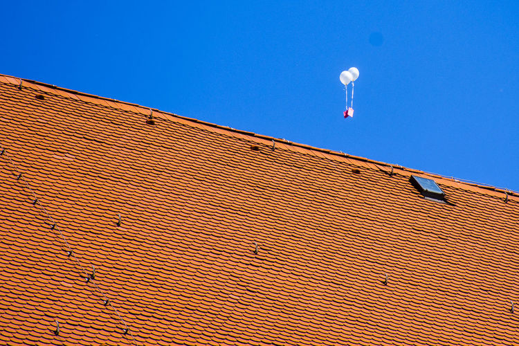 House Roof Against Balloons Flying In Clear Blue Sky
