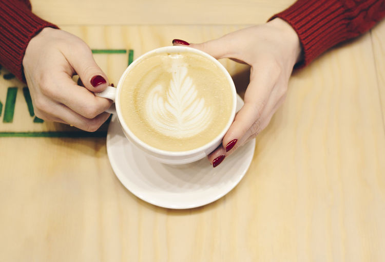 Women's hands with a Cup of cappuccino in a cafe Coffee Cup Cup Refreshment Mug Coffee Drink Food And Drink Coffee - Drink One Person Human Hand Real People Hand Table Holding Froth Art Indoors  Frothy Drink Crockery Saucer Cappuccino Hot Drink Latte