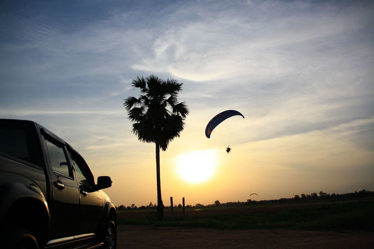 Paramotor flies before the sunset in Thailand. Paramotor Cloud - Sky Adventure Plant Sport Extreme Sports Mode Of Transportation Silhouette Beauty In Nature Motor Vehicle Paragliding Nature Parachute Transportation Sunset Car Field Tree Leisure Activity Land Vehicle Sky