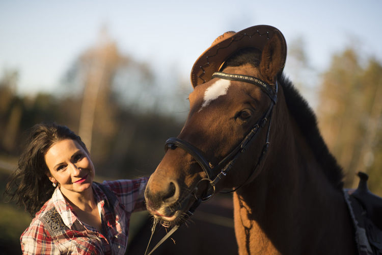 Young woman playing with  horse in sunny day inside corral ranch - love between people and animals