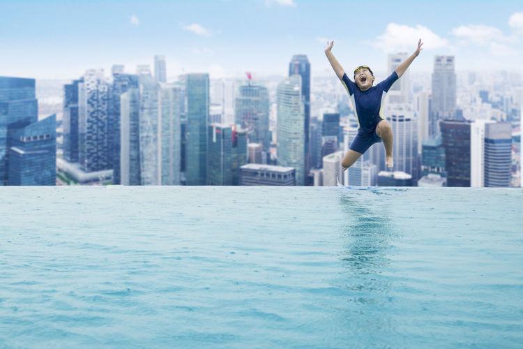 Boy Jumping In Swimming Pool Against Cityscape
