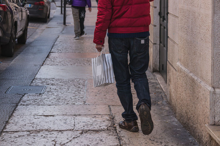 Low section of man standing with a bag