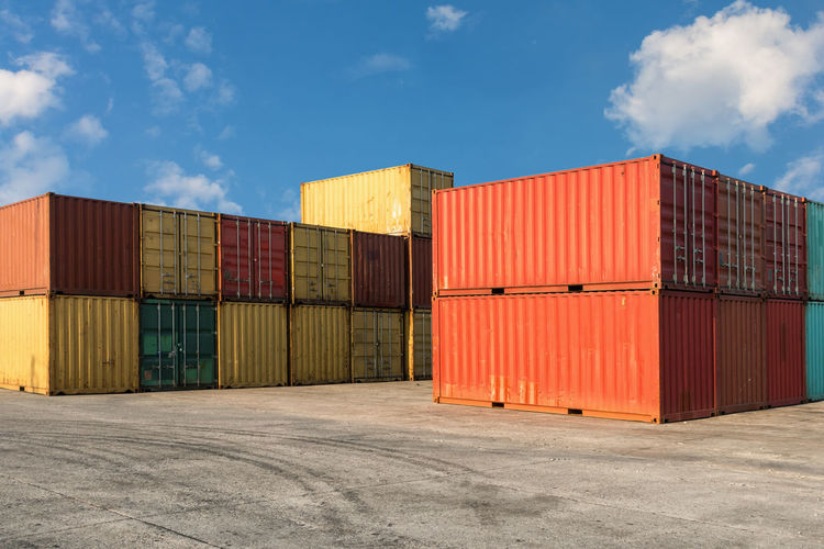 Stack of multi colored cargo containers at harbor against sky