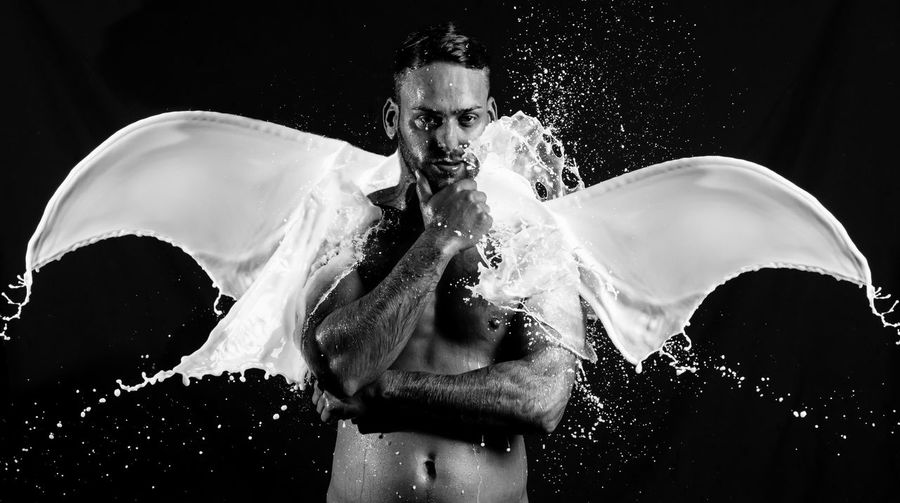 Portrait Of Shirtless Man By Milk Splashing In Angel Shape Against Black Background
