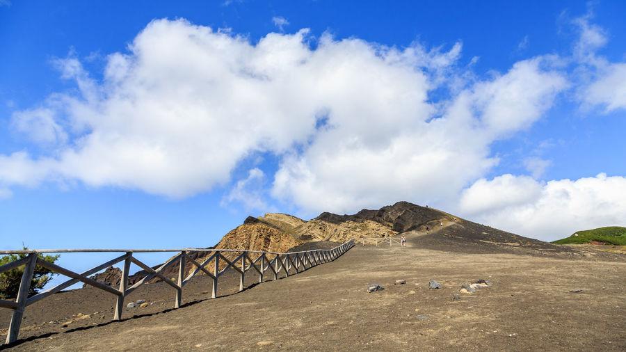 Road by bridge against blue sky