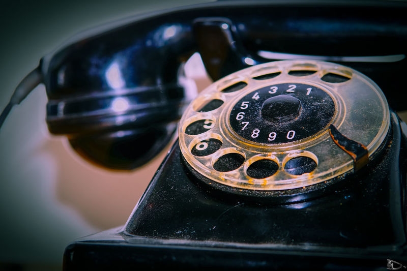 Close-Up Of Black Rotary Phone By Wall