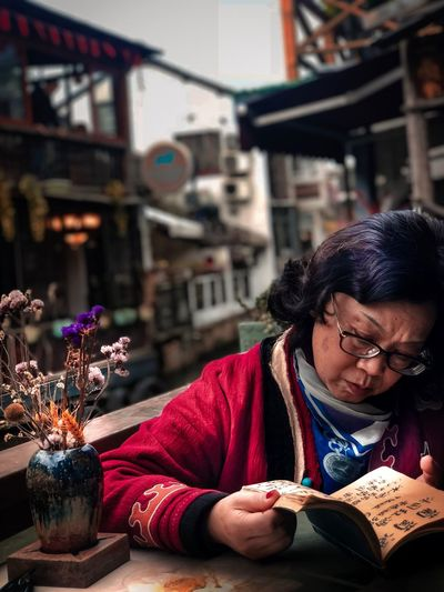 Woman reading book at cafe in city