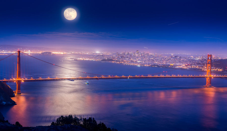 Illuminated Golden Gate Bridge Over Sea Against Full Moon At Night