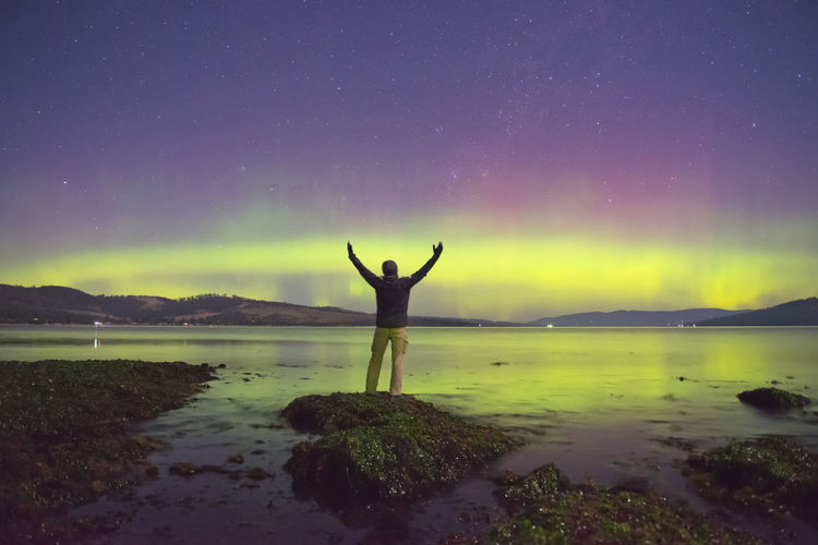 Rear view of man with arms raised standing on rock at lakeshore against northern lights at night