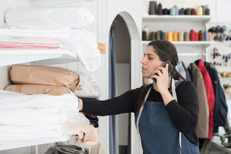 Woman using mobile phone in store