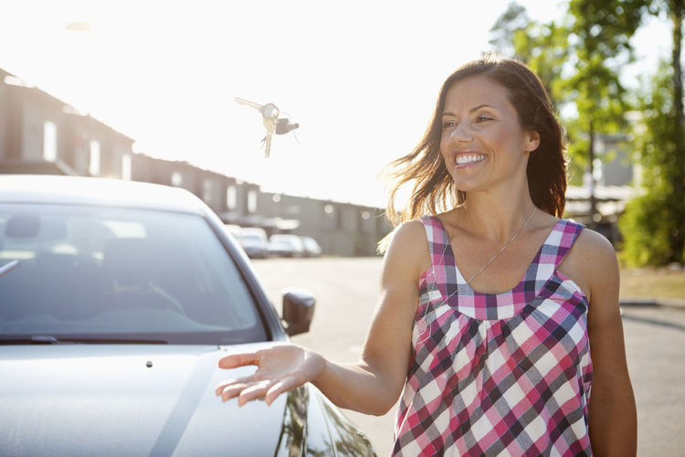 Portrait of smiling young woman standing by car in city