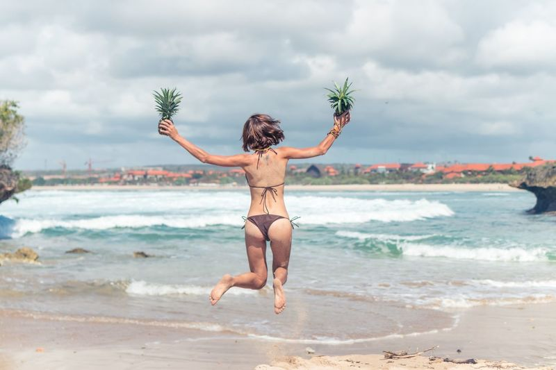 Rear view of woman in bikini holding pineapples while jumping against sea at beach