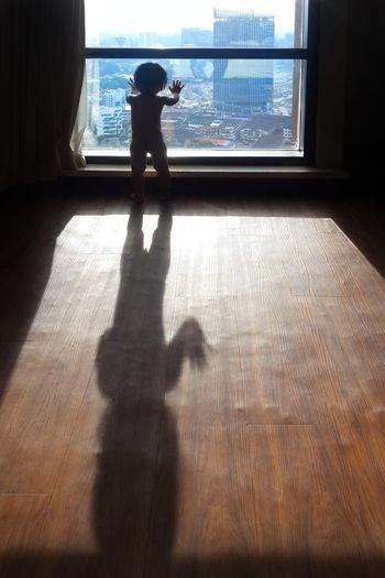 Shadow of man on hardwood floor at home