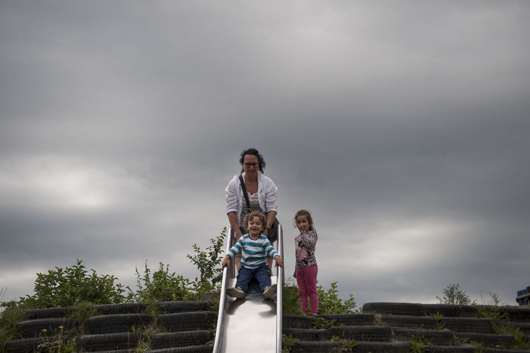Mother with son and daughter against cloudy sky