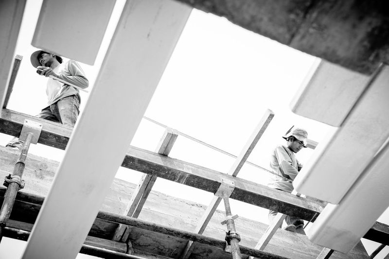 the worker Workers Architecture Built Structure Day Low Angle View Men People Railing Real People Sitting Staircase Standing Two People Work Man Workers At Work Working